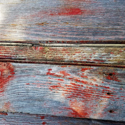 This siding has been painted at some point in time and has weathered over the years. Varying degrees of weathering can leave the red color from just a faint trace over a natural grey to a more solid red color.
